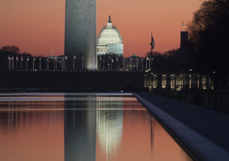 The sun begins to rise on the last day of the year, with the base of the Washington Monument and US Capitol Building reflected in the Lincoln Memorial Reflecting Pool, in Washington DC.