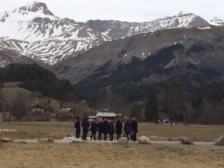 Families of victims of the Germanwings crash stand at the memorial closest to the crash site, looking at the mountains where their loved ones died.