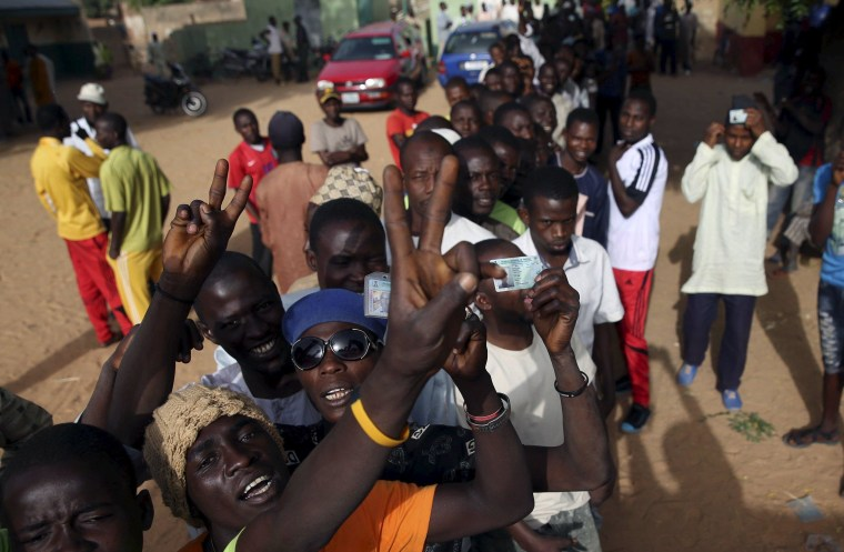 Image: Men wait in line to register to vote in a poling station during elections in Kano