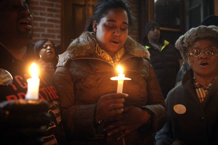 Image: Eric Garner's daughter Erica takes part in candlelight vigil at the site where her father died in July last year after being put in a chokehold, during a Martin Luther King Day service in New York