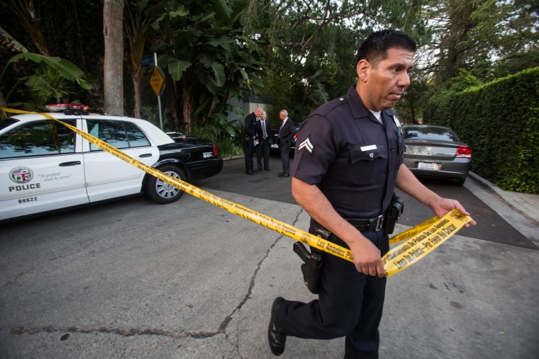 Image: A police officer creates a perimeter outside a home in the Hollywood Hills area