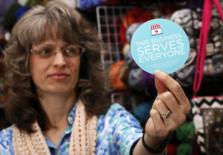 Image: Business owner holds sticker to place outside her shop in Lafayette, Indiana