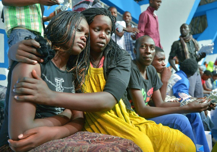 Image: A survivor of an attack by islamist gunmen claimed by al Shabab on a university campus in Garissa, northern Kenya is comforted by a colleague