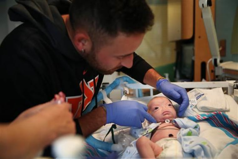 Troy Thompson tends to his son, Eli at the NICU at USA Children's & Women's Hospital in Mobile, Ala., on March 19, 2015.