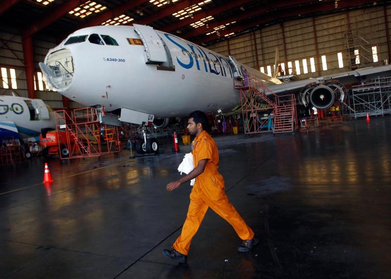 Image:An engineer walks past a Sri Lankan Airlines jet on Feb. 10