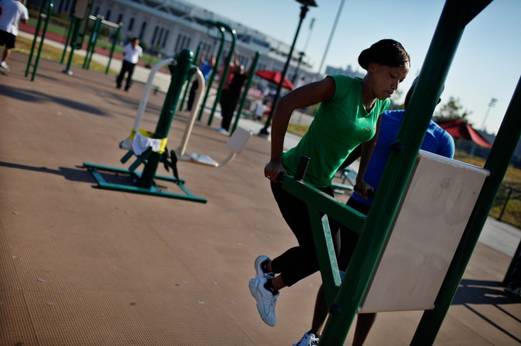 Image: A woman works out in an outdoor exercise area at Macombs Dam Park in the Bronx section of New York City