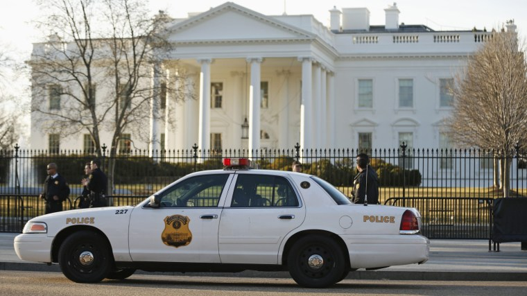 Image: Members of the U.S. Secret Service keep watch at the fence surrounding the White House in Washington
