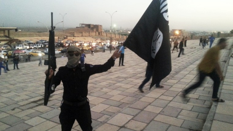 Image: A fighter of the ISIS holds a flag and a weapon on a street in Mosul