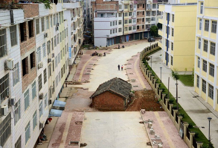 """Image: A \""""nail house\"""", the last building in the area, sits in the middle of a road under construction in Nanning"""