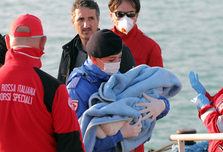 A Red Cross officer carries a baby wrapped in a blanket after migrants disembarked at the Sicilian Porto Empedocle harbor, Italy, Monday, April 13, 2015. Italy's Coast Guard helped save 144 migrants Monday from a capsized boat in the waters off Libya and spotted nine bodies. It was the most dramatic of numerous rescue operations that brought thousands to safety in recent days, as good weather has encouraged the desperate to set out on smugglers' vessels. The overturned boat was spotted 80 miles north of Libya, Coast Guard Cmdr. Filippo Marini told The Associated Press in a telephone interview.