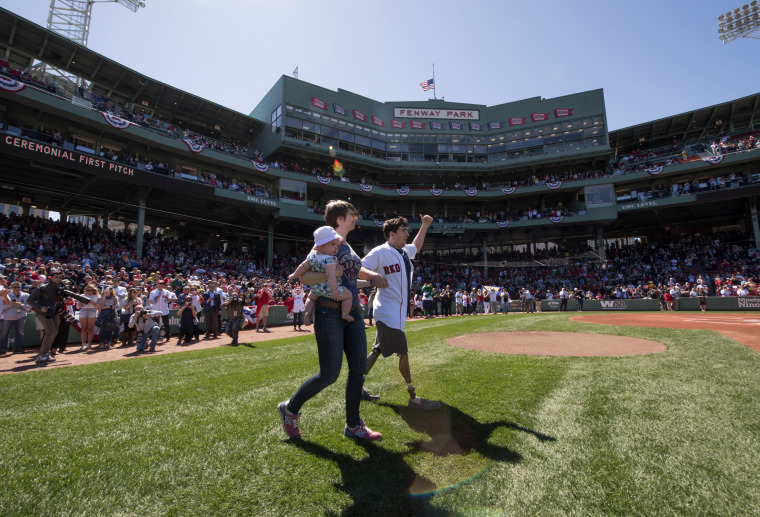 Boston Marathon bombing victim Jeff Bauman heads to the mound with his wife Erin Hurley to throw out a ceremonial first pitch before a game between  the Boston Red Sox and  the Washington Nationals on April 15, 2015 at Fenway Park in Boston, Massachusetts.