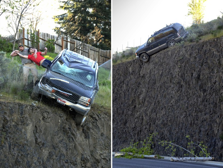 Jason Warnock pulls the driver from a SUV Wednesday morning after the vehicle left Mayfair Drive in Lewiston and traveled downhill, stopped by a chain link fence just short of a vertical drop onto the Bryden Canyon Road.