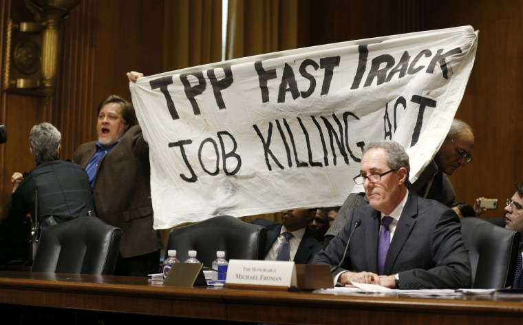 Image: TPP protester holds up a sign during Froman trade hearing on Capitol Hill in Washington