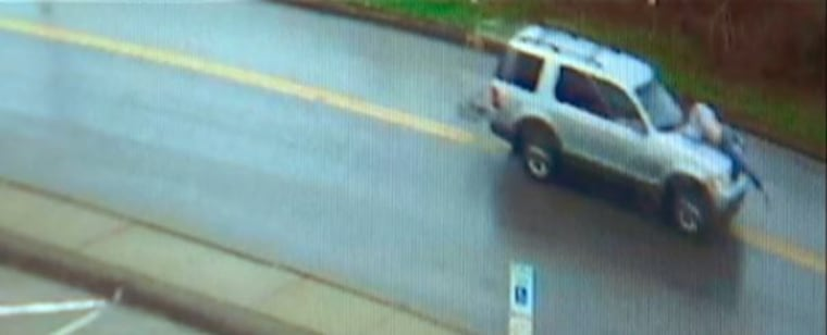 Surveillance video shows a man hanging onto the hood of a car in Springdale, Pennsylvania.