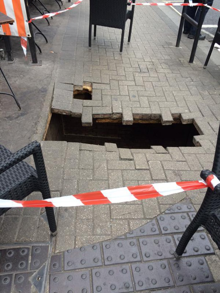 A woman was literally swallowed by the ground below her when the London sidewalk she was walking along collapsed on Thursday morning, according to officials and witnesses.