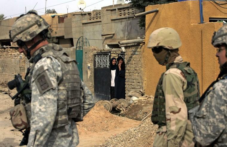 Iraqi women look at U.S. soldiers and their Iraqi interpreter patrolling in eastern Baghdad in 2006.