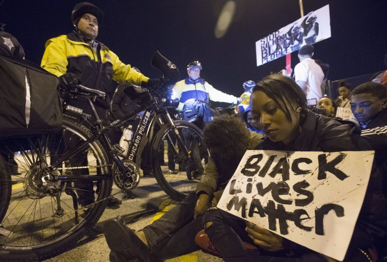 Image: Protesters sit in during a moment of silence in front of a line of police officers, in solidarity with protests over the Baltimore death of Freddie Gray, in Chicago