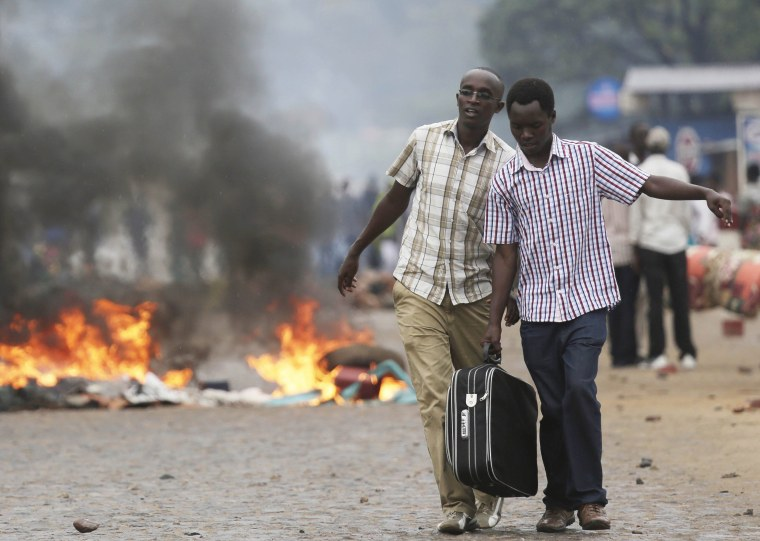 Two men carry a suitcase past a burning barricade in Bujumbura, Burundi Thursday, April 30, after the government issued and ordered for all university campuses to close down.