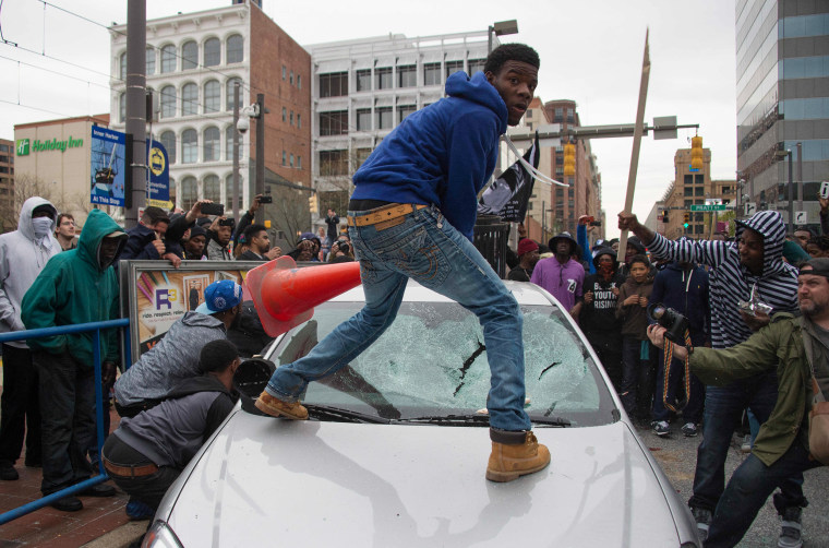 Image: Demonstrators destroy the windshield of a Baltimore Police car