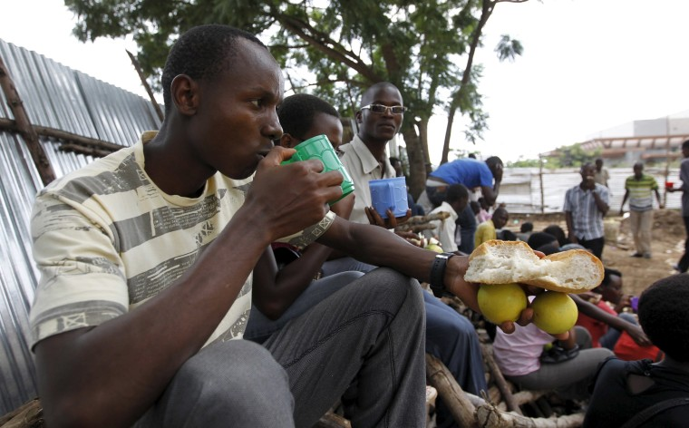 Image: Students from a Burundi university eat food rations as they camp outside the U.S. embassy in the capital Bujumbura