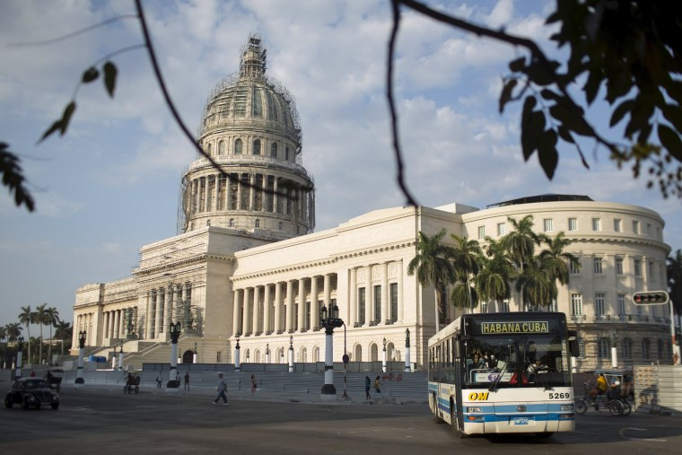 Image: A public bus passes by the Capitol in Havana