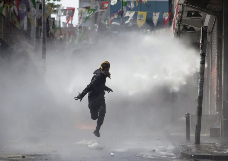 Image: A masked protester runs away from a water cannon's jet during clashes with police in Okmeydani neighbourhood in Istanbul