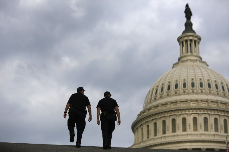 Image: U.S. Capitol Police return to patrol after a brief meeting to discuss how to handle tourists turned away from the shuttered visitor's center at the U.S. Capitol in Washington