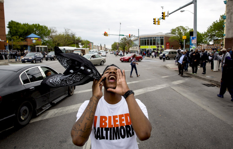 People react as police line up at North Ave and Pennsylvania Ave in Baltimore, Maryland May 1.