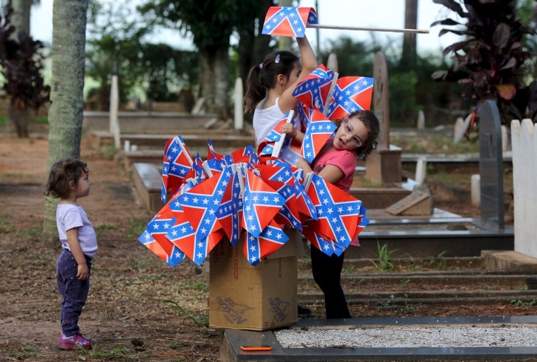 Image: Descendants of American Southerners play with confederate flags in a cemetery in Santa Barbara D'Oeste, Brazil