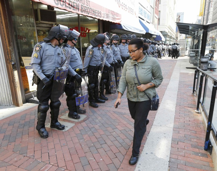 Image: A pedestrian walks by as riot police take position in front of businesses on Howard Street in downtown Baltimore
