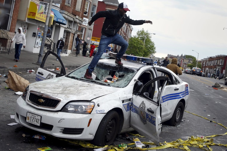 Image: Demonstrators jump on a damaged Baltimore police department vehicle during clashes in Baltimore