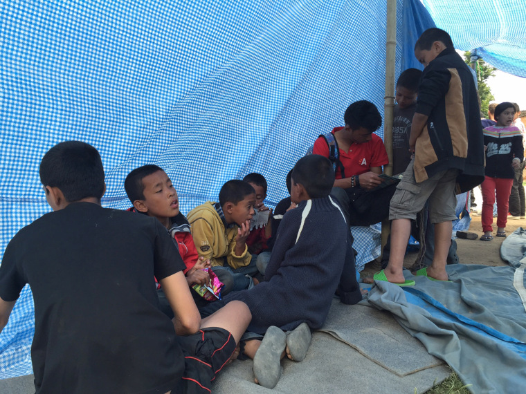 Children underneath the tarp in the yard next to the house where they have taken shelter.