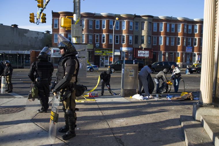 Maryland state troopers stand guard, Tuesday, as residents clean up after an evening of riots following the funeral of Freddie Gray on Monday, in Baltimore.