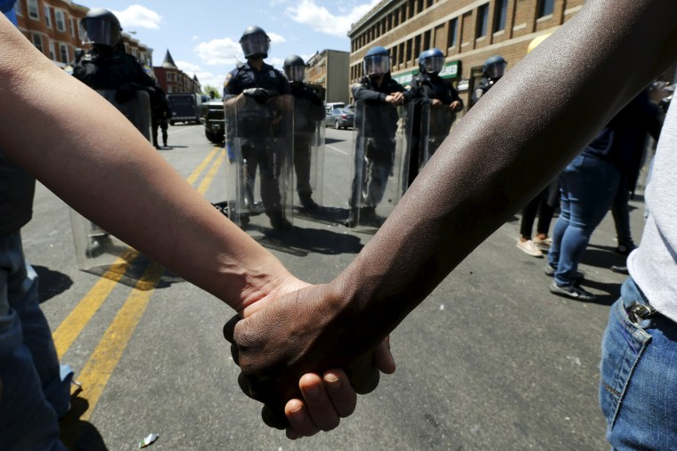 Image: Members of community hold hands in front of police officers in riot gear outside recently looted and burned CVS store in Baltimore