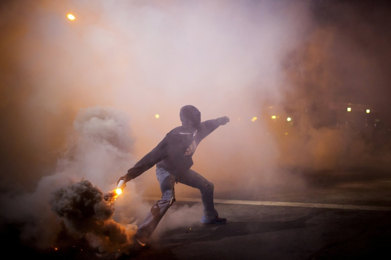 Image: A protester throws a gas canister back at police during clashes at North Ave and Pennsylvania Ave in Baltimore