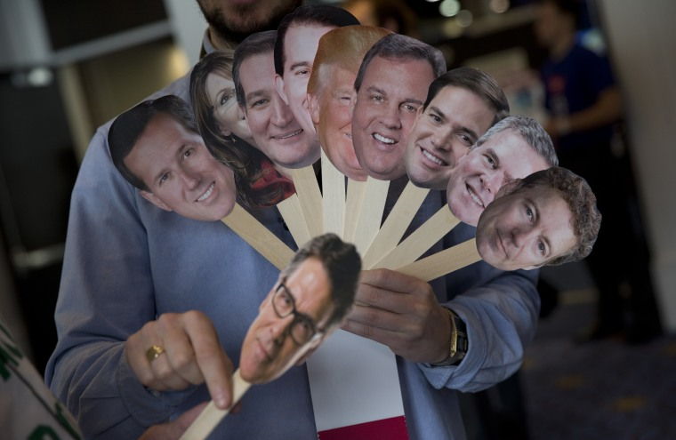 "Adam Gabbatt of The Guardian newspaper holds images of possible Republican candidates, from left, former Pennsylvania Sen. Rick Santorum, former Alaska Gov. Sarah Palin, Sen. Ted Cruz, R-Texas, Wisconsin Gov. Scott Walker, Donald Trump, New Jersey Gov. Chris Christie, Sen. Marco Rubio, R-Fla., former Florida Gov. Jeb Bush, Sen. Rand Paul, R-Ky., and, former Texas Gov. Rick Perry, bellow, as he interviews Howard ""Cowboy"" Woodward during the Conservative Political Action Conference (CPAC) in National Harbor, Md., Thursday, Feb. 26, 2015. (AP Photo/Carolyn Kaster)"