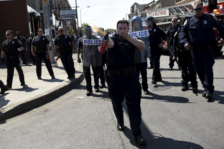 Image: A law enforcement officer uses pepper spray to disperse the crowd at the intersection of North and Pennsylvania Avenues in Baltimore