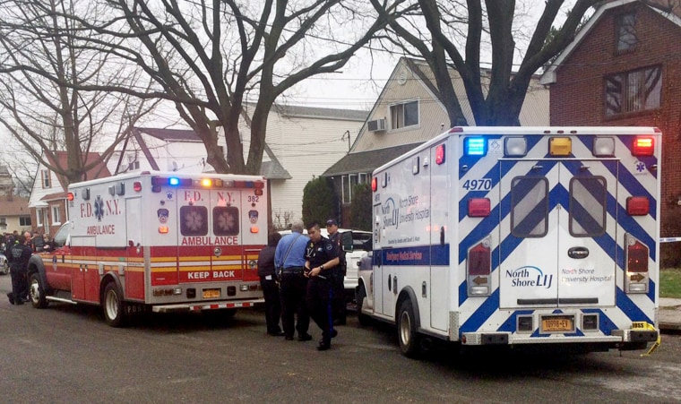 Image: Emergency personel gather near a home where police say four people were found dead in an apparent carbon monoxide poisoning