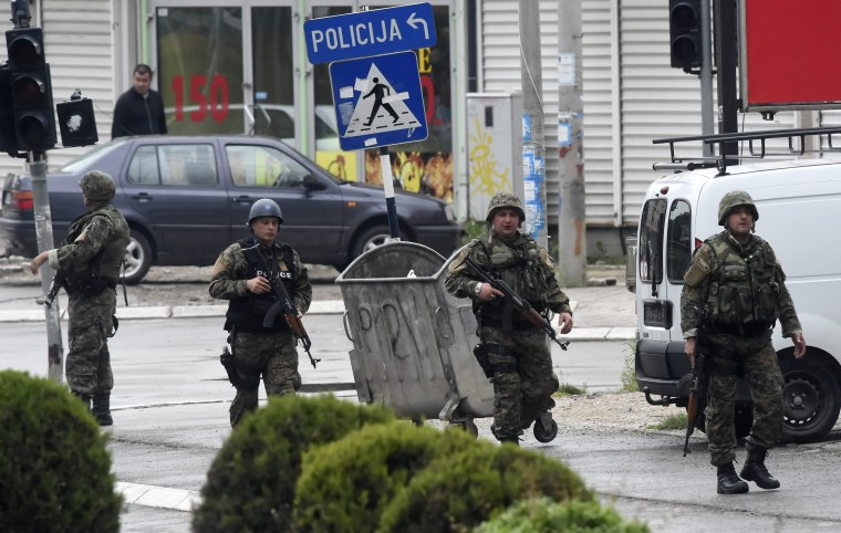 Police officers walk on a street as Macedonian special forces engage in a police action against an alleged group of unidentified armed group, in Kumanovo, the Former Yugoslav Republic of Macedonia, 09 May 2015. Unofficial sources claim three officers were injured during an action against an armed group, but the number was not confirmed by police.