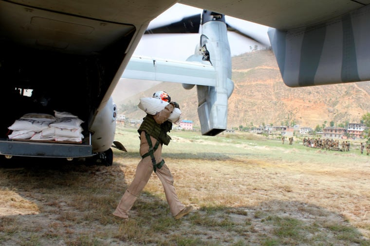 Image: A U.S. Marine unloads rice from a Boeing V-22 Osprey in the Nepali village of Panchka.