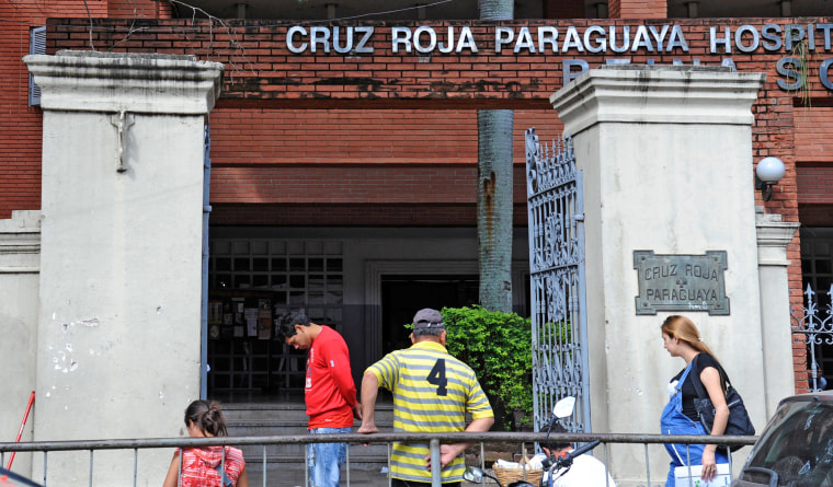 People remain at the entrance of the Red Cross Hospital where a 10-year-old girl who was raped by her stepfather and is now five months pregnant is assisted in Asuncion on May 8, 2015.