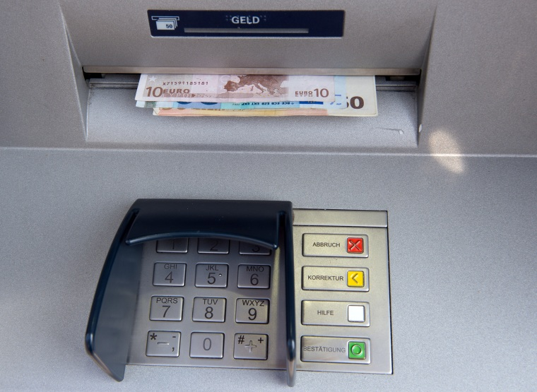 Bank notes are withdrawn at ATM in Berlin.