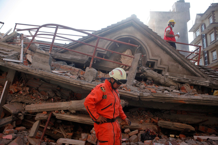 Image: A Mexican rescue worker stands at the site of a building that collapsed in an earthquake in Kathmandu, Nepal