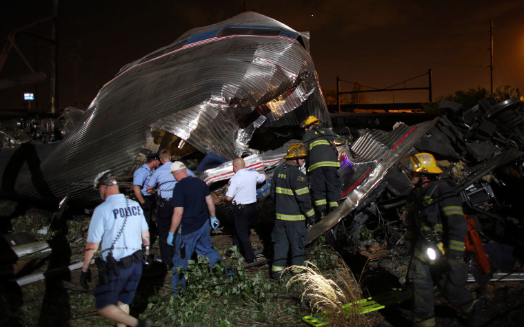 Image: Emergency personnel work the scene of a train wreck