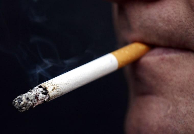 Image: A man smokes a cigarette