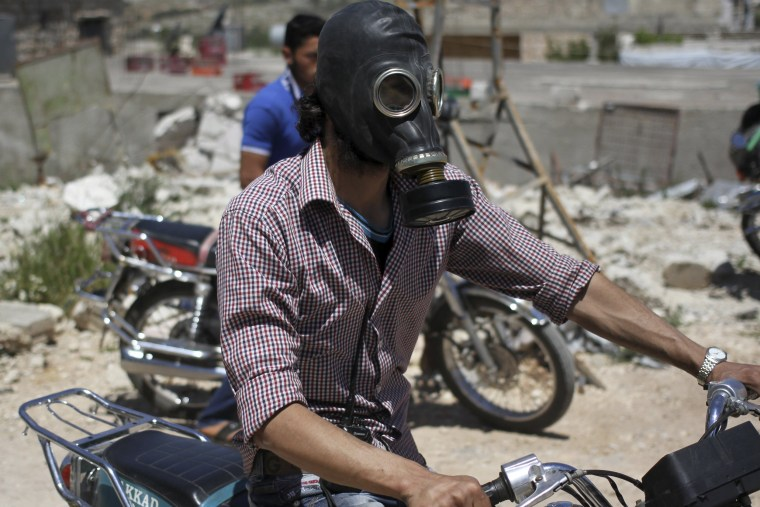 Image: A man drives his motorcycle as he wears a gas masks after what activists said was a chlorine gas attack on Kansafra village at Idlib countryside