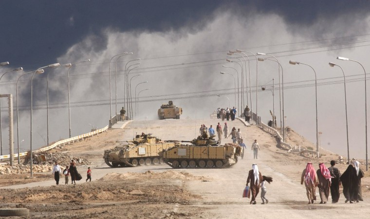 Image: Civilians on foot pass tanks on a bridge near the entrance to the besieged city of Basra March 29, 2003 in Iraq.