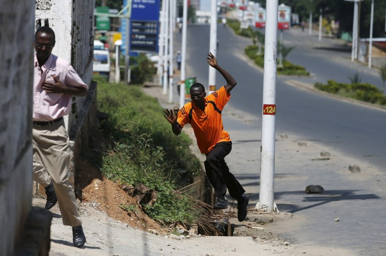Image: Men run for cover after they hear gunfire in a street in Bujumbura