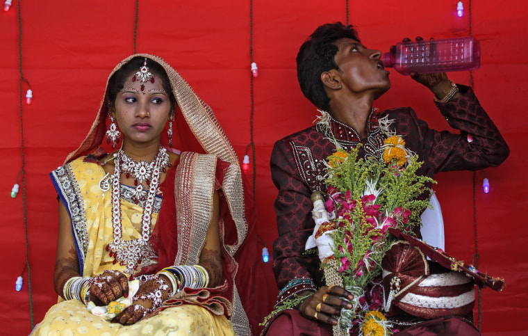 An Indian groom drinks water to cool off from heat on a hot afternoon as the bride looks on during a mass marriage ceremony on the occasion of the Akshaya Tritiya festival in Mumbai, India, 21 April 2015.