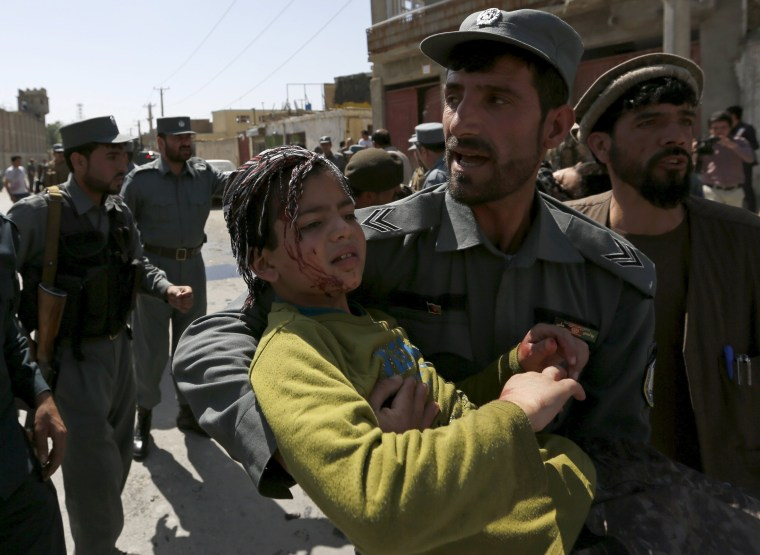 Image: A policeman carries an injured boy from site of an attack in Kabul, Afghanistan